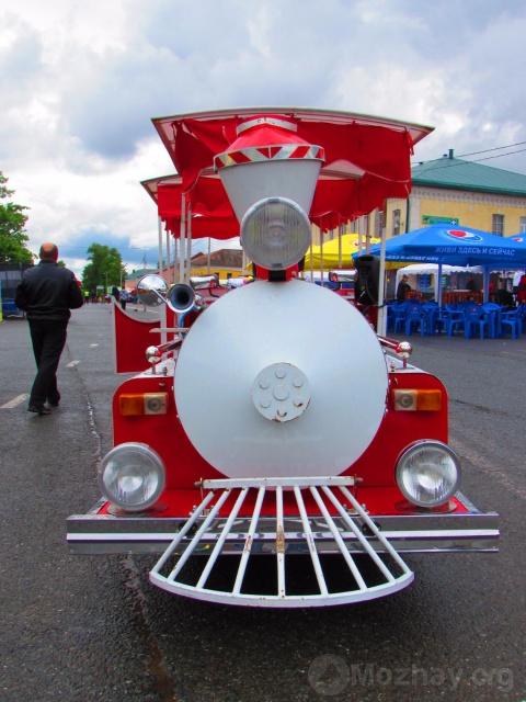 Трактор-паровозик на дне города.